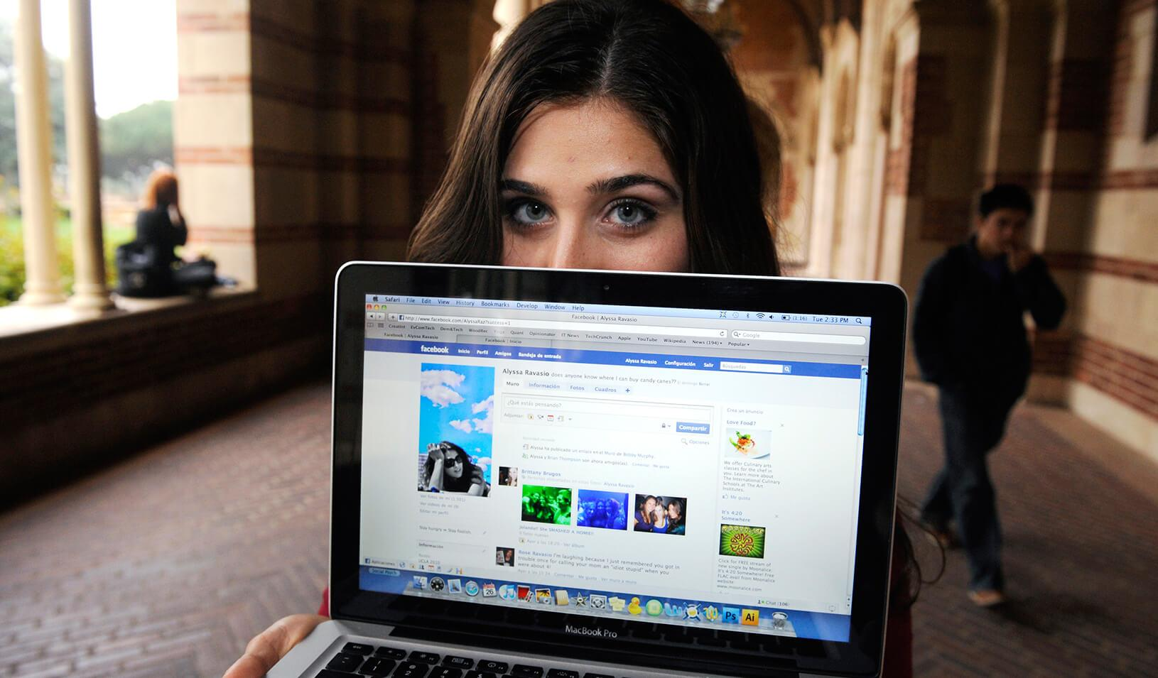 A girl holding a computer that has Facebook on it