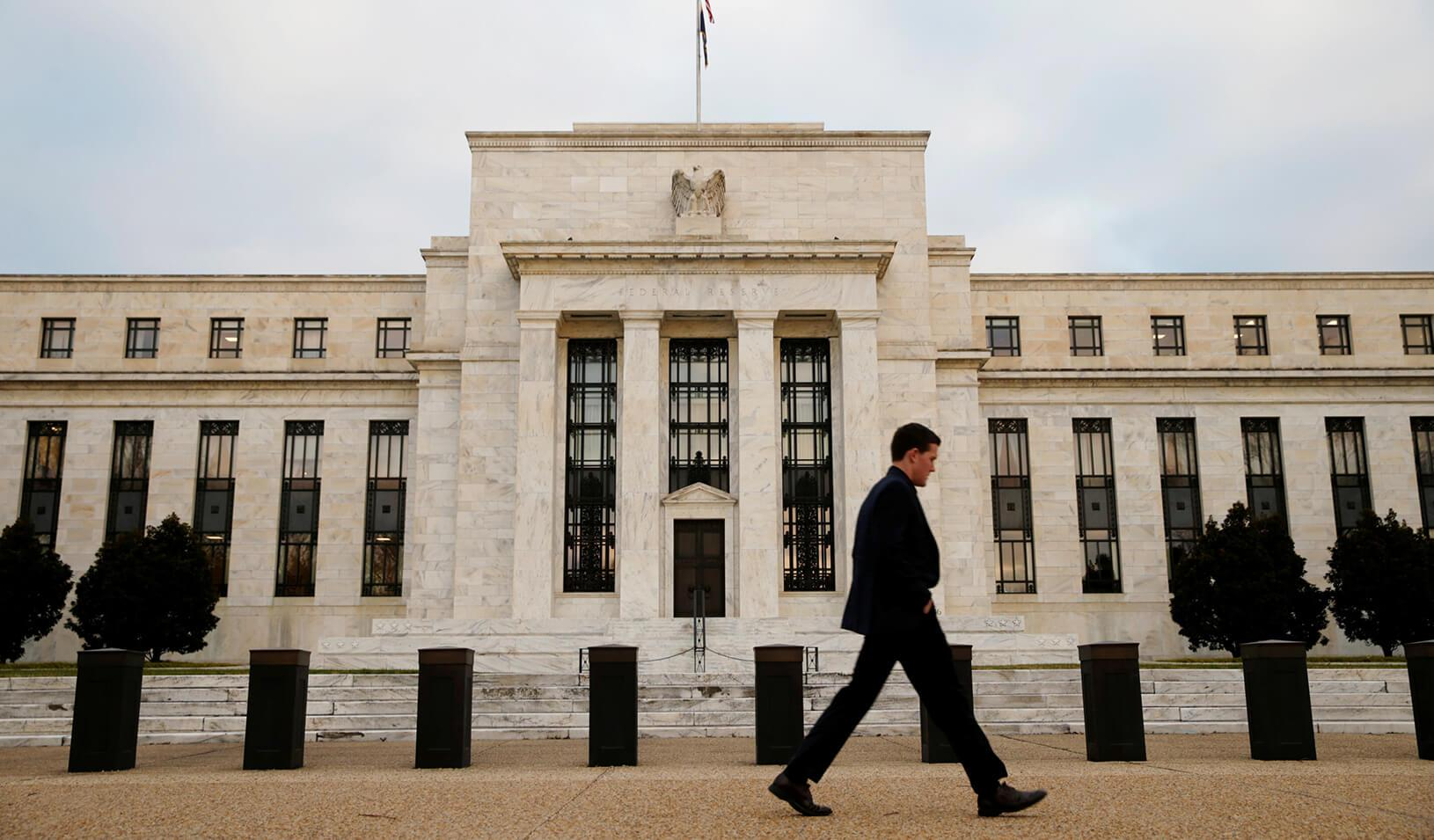 A man walks past the Federal Reserve Bank in Washington, D.C.
