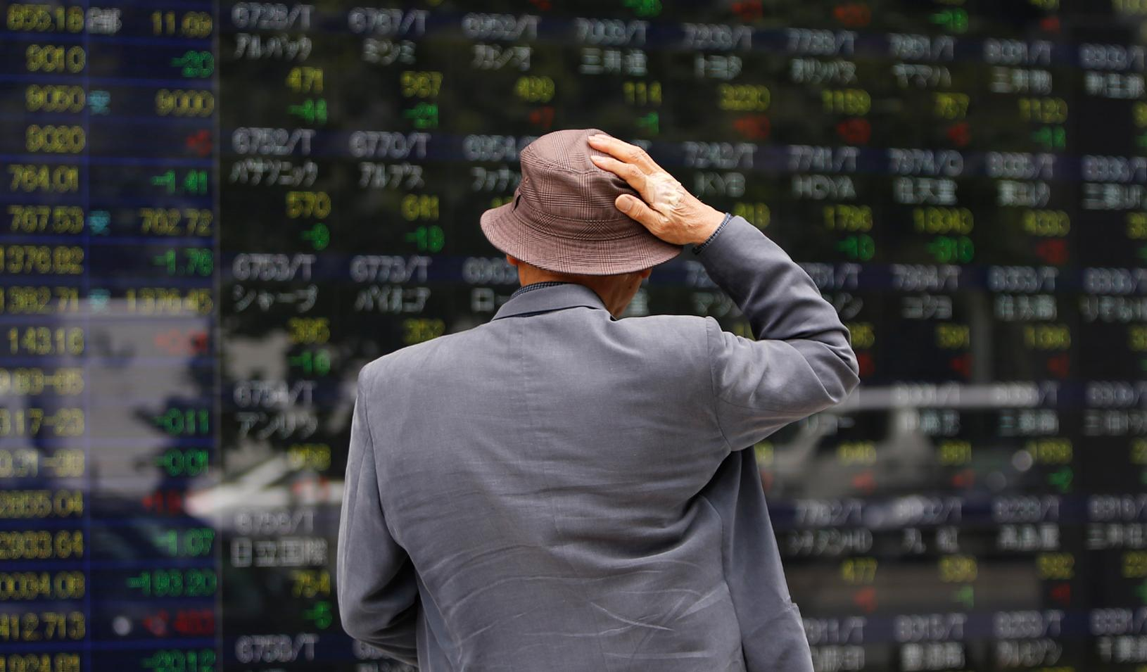 A man looks at a stock quotation board outside a brokerage. Credit: Reuters/Toru Hanai