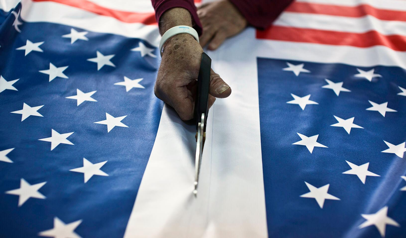 A worker at a factory in Kfar Saba near Tel Aviv cuts fabric printed with U.S. flags. | Reuters/Nir Elias