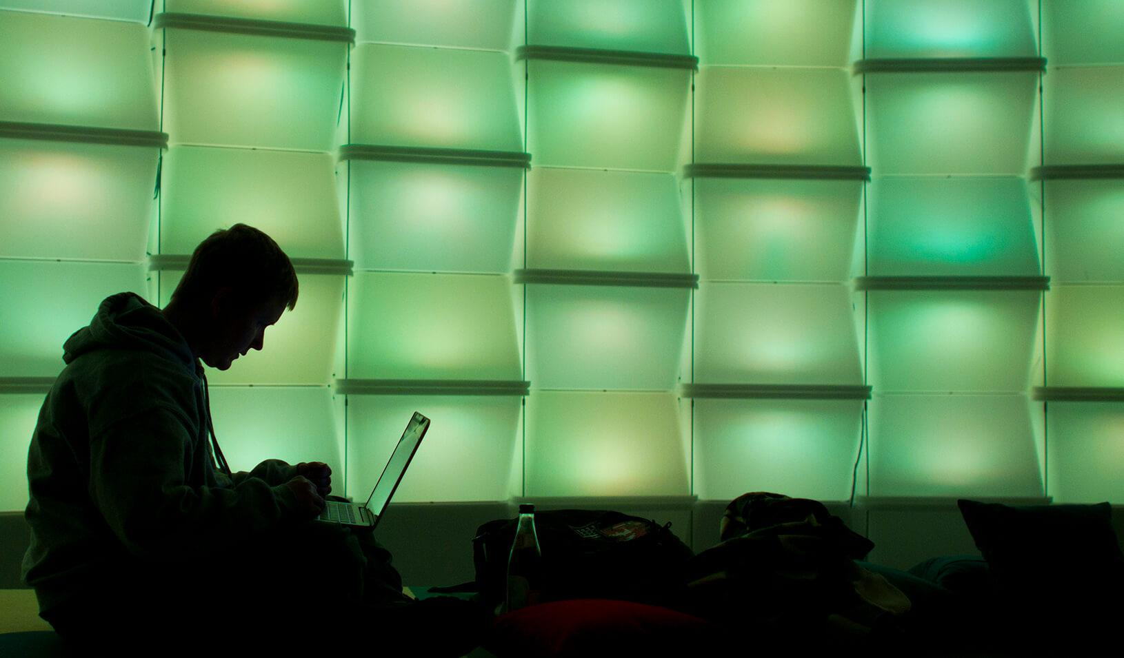 A woman uses a computer in a lounge area.