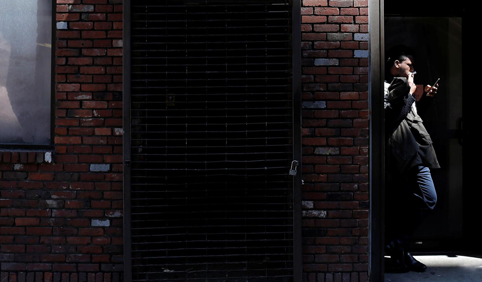 A man smokes a cigarette in a doorway in downtown Boston, Massachusetts. | Reuters/Brian Snyder