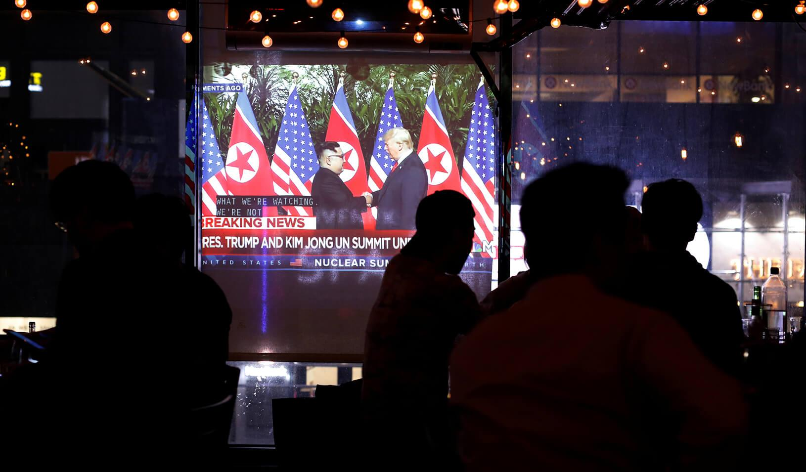 People gather in the WABar to watch a broadcast on television as U.S. President Donald Trump meets North Korean leader Kim Jong Un, Credit: Reuters/Andrew Kelly