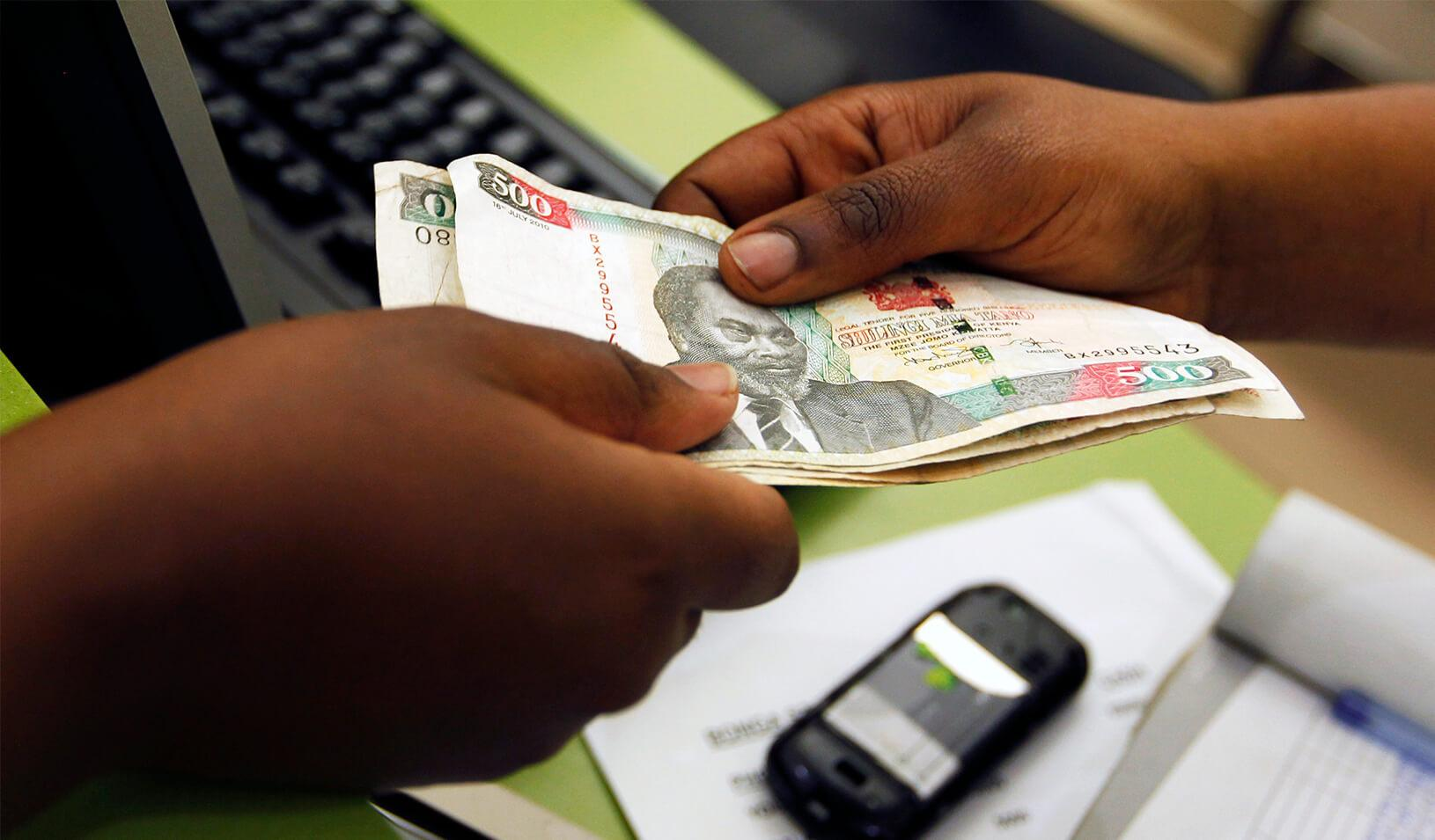 A customer conducts a mobile money transfer, known as M-Pesa, inside the Safaricom mobile phone care centre in the central business district of Kenya's capital Nairobi
