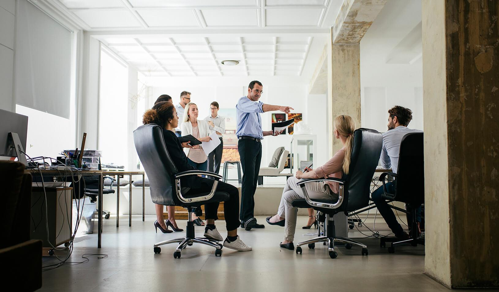 A manager, standing among his employees, points at one of them during a meeting. Credit: iStock/Thomas_EyeDesign