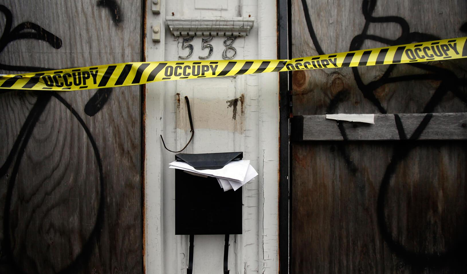 The door of an abandoned house with caution tape in front of it
