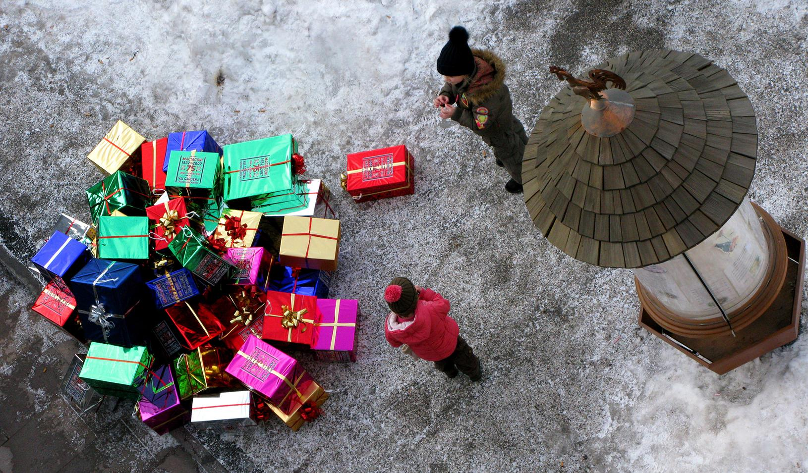 Children next to a pile of gifts