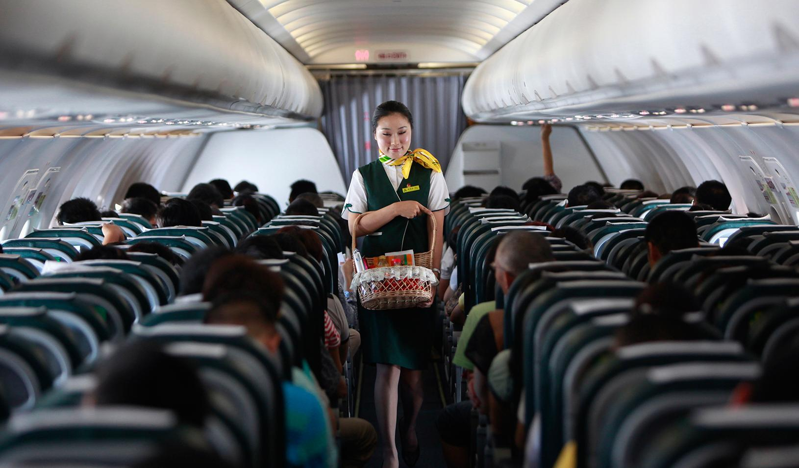 A flight attendant walking down the aisle of a plane