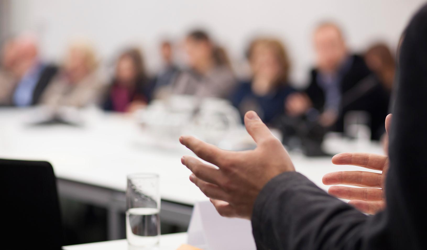 A person's hands gesturing while he or she is speaking at a meeting