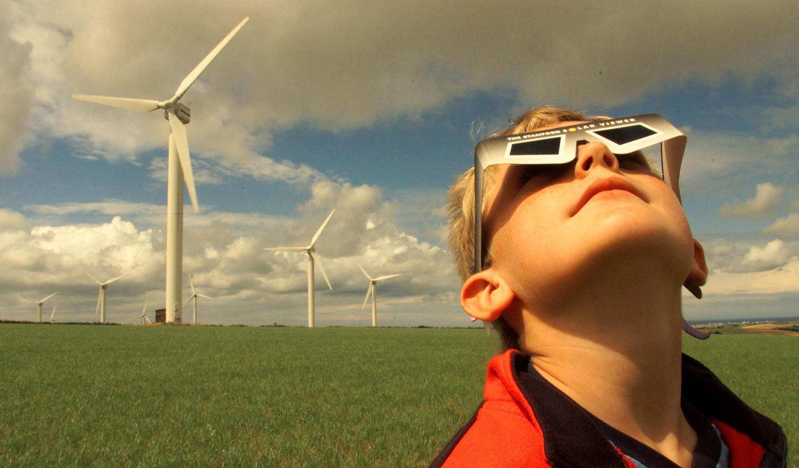 Boy wearing eclipse viewing glasses near a wind farm