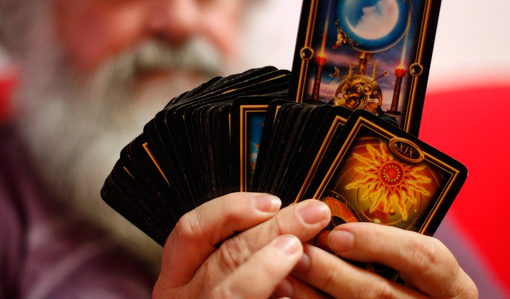 A man holding a deck of magic cards