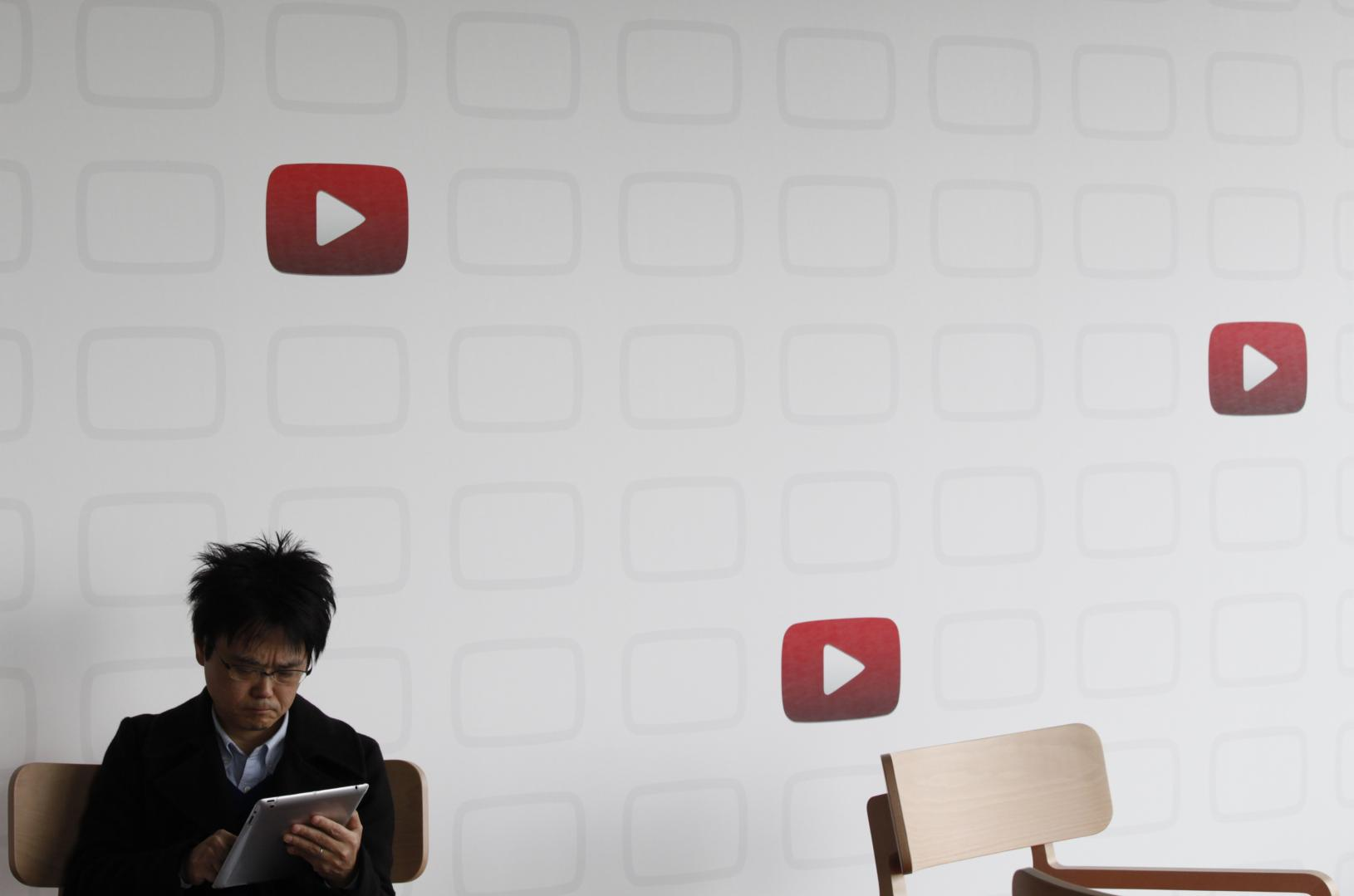 A man sits in front of a wall with the YouTube logo on it.