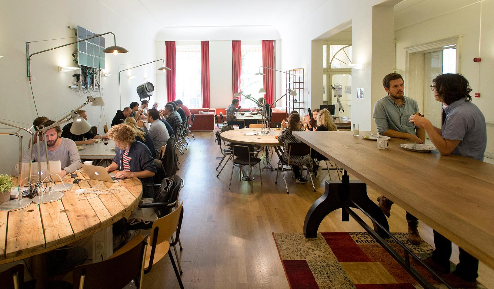 People working at various tables in an office space