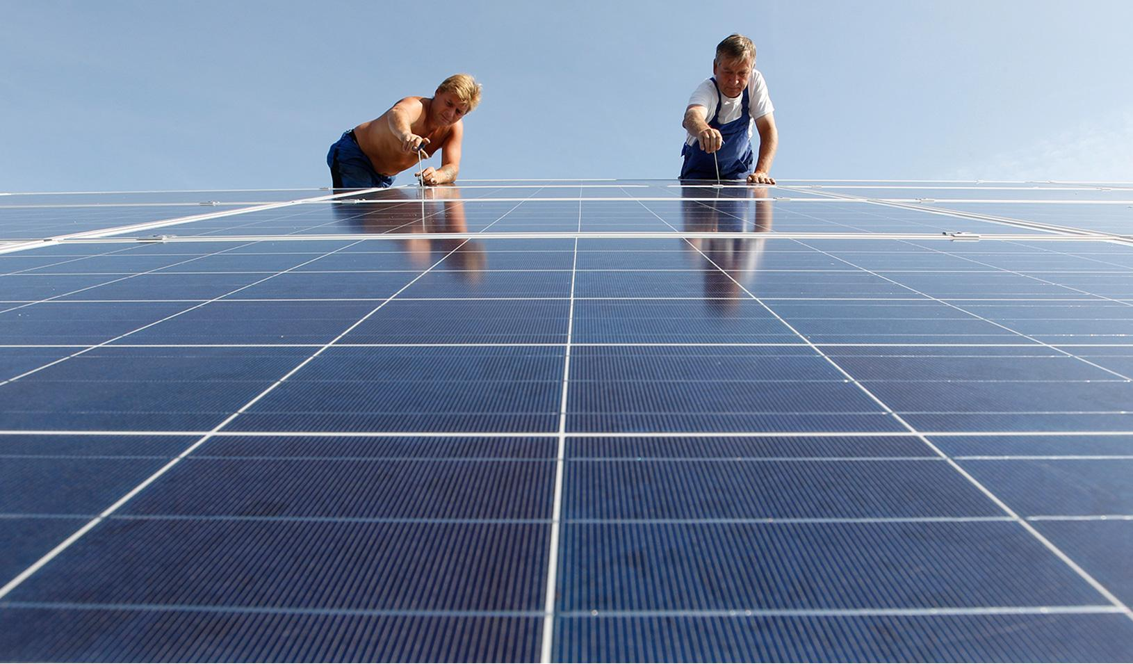 Construction workers fix solar panels for a new solar power plant in ...
