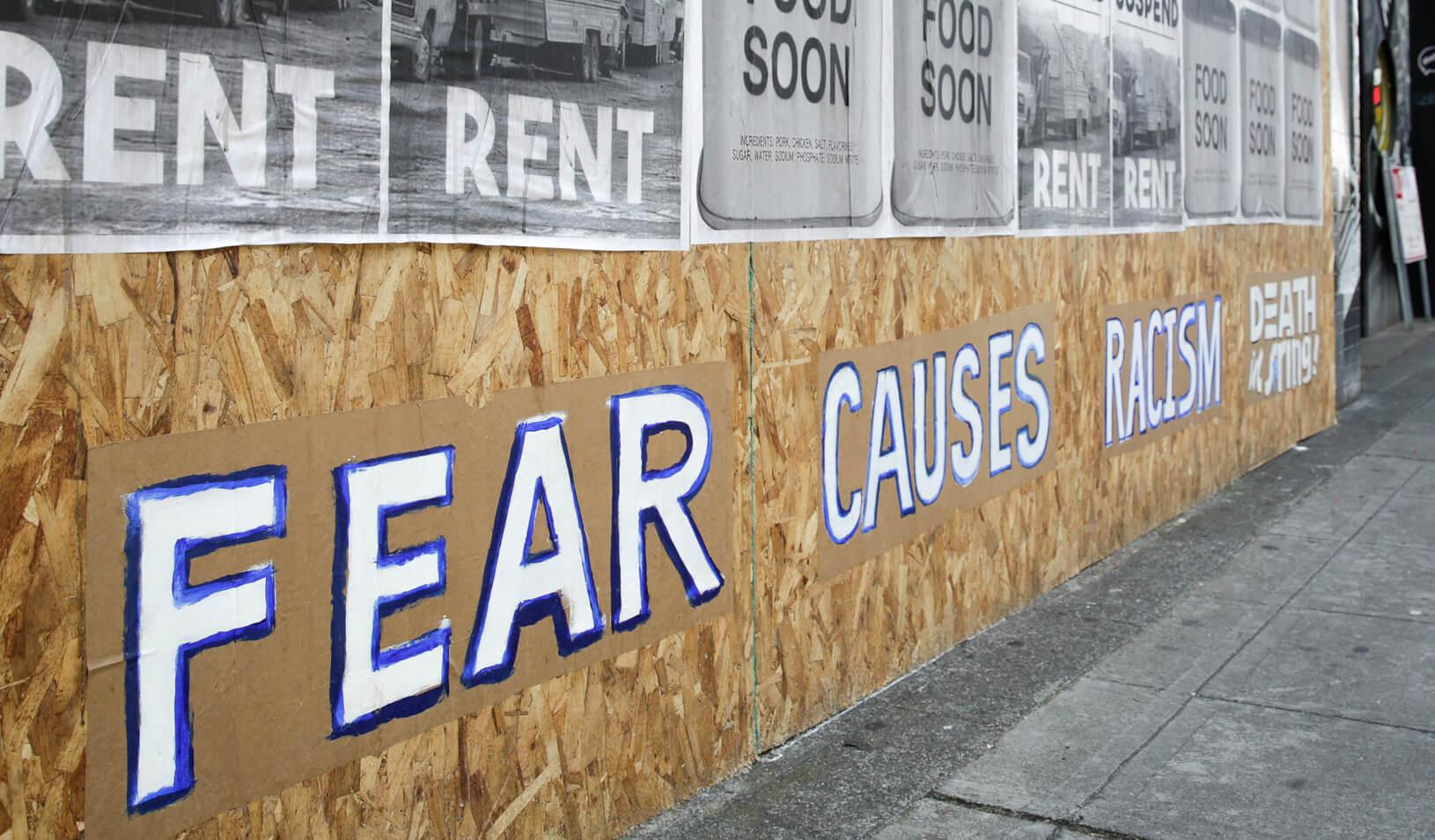 """Signs that read """"suspend rent"""" and """"fear causes racism"""" are pictured on a boarded-up business in Seattle during the outbreak of the coronavirus disease (COVID-19). Credit: Reuters/Jason Redmond"""