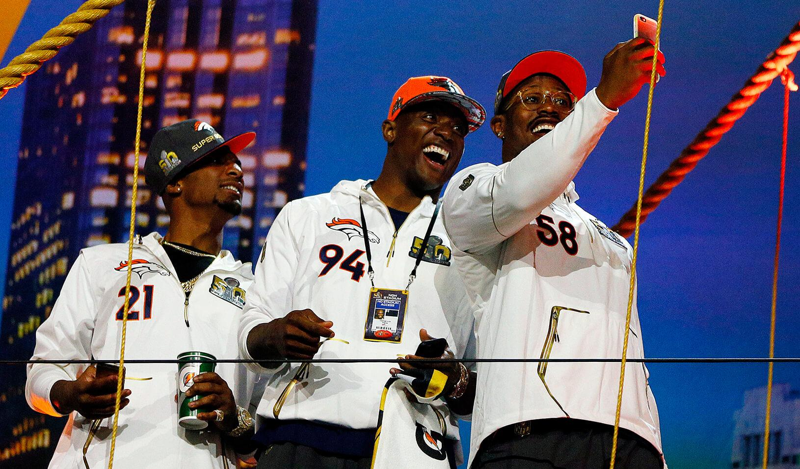 Three Denver Bronco players take a selfie during Super Bowl 50 Opening Night media day.