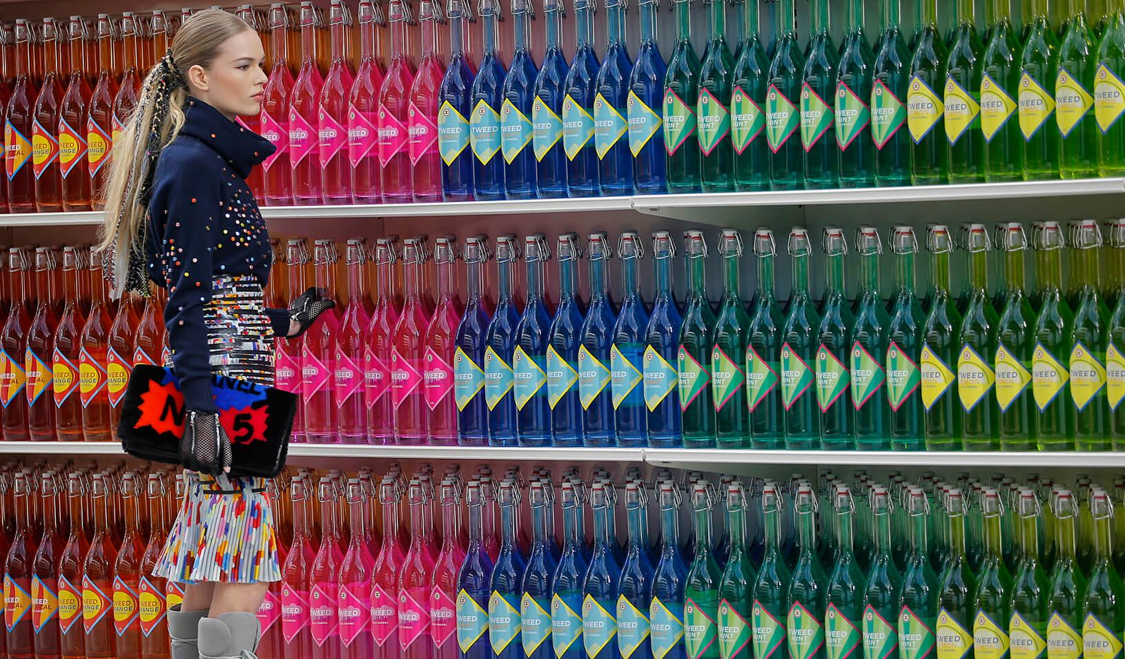 A woman stands in front of shelves of beverages