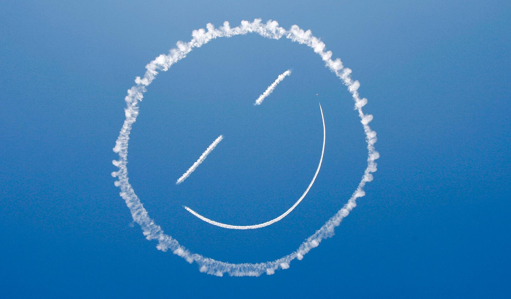 "A plane ""sky writes"" a smiley face in the sky."