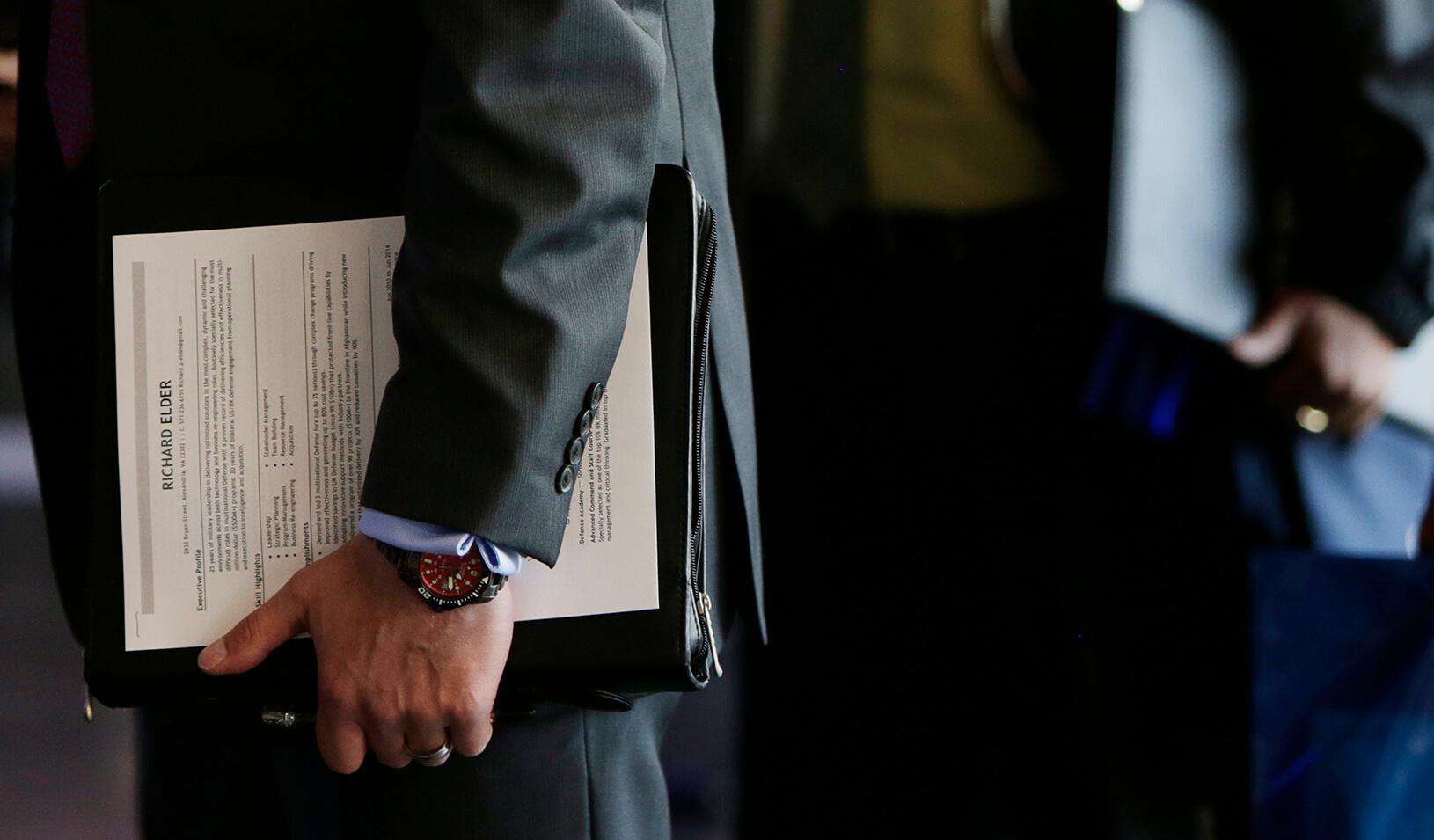 An applicant holds his resume at a hiring fair for job seekers