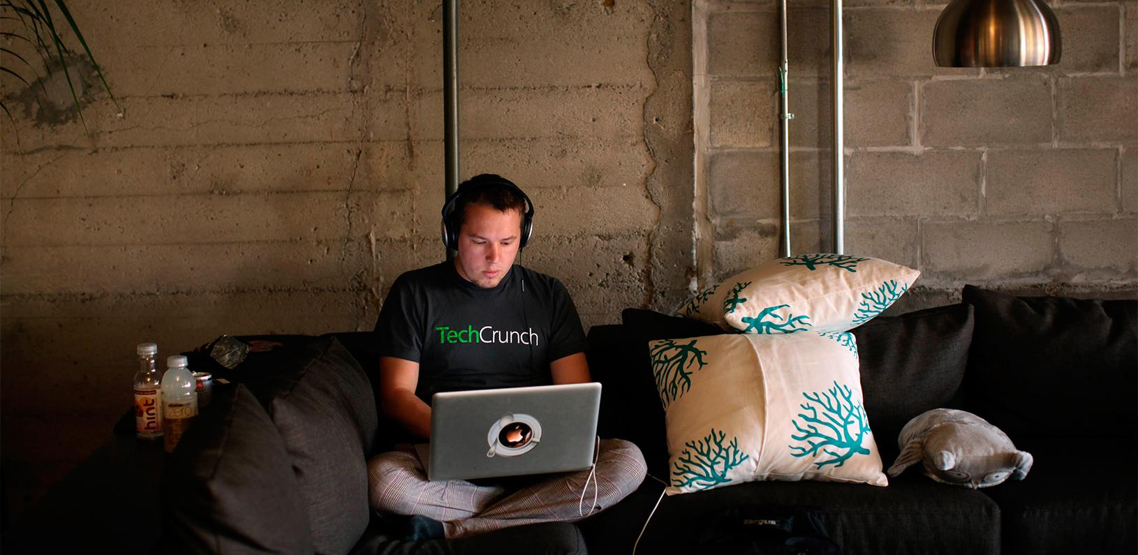 Engineer Buford Taylor sits on a couch as he works on his computer at Eventbrite headquarters in the South of Market area in San Francisco, California