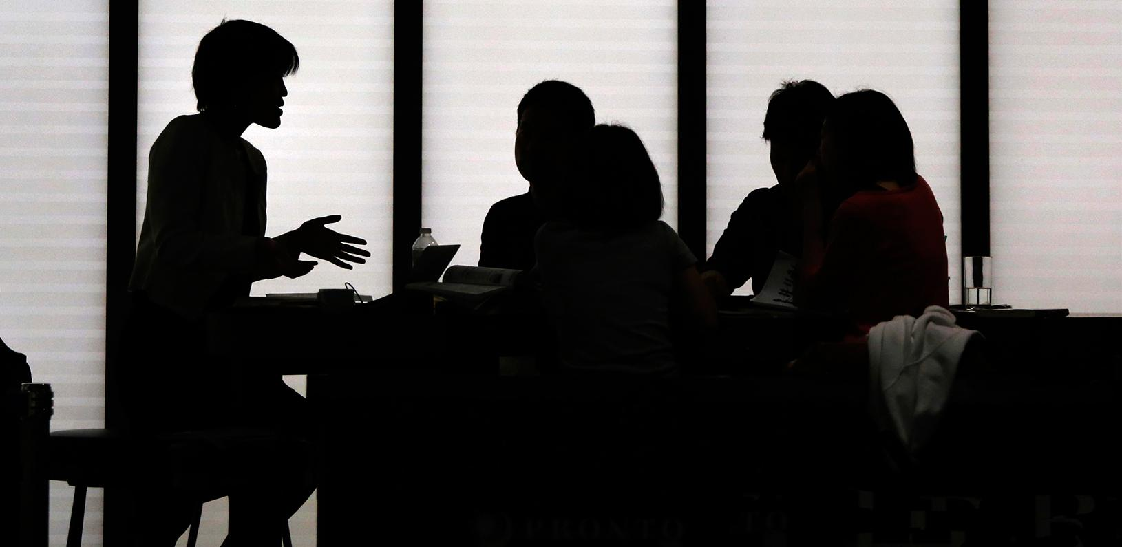 Silhouetted people holding a meeting