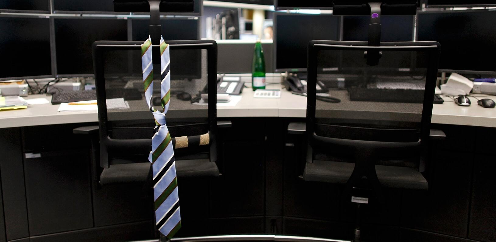 a tie hanging on the back of an empty work chair