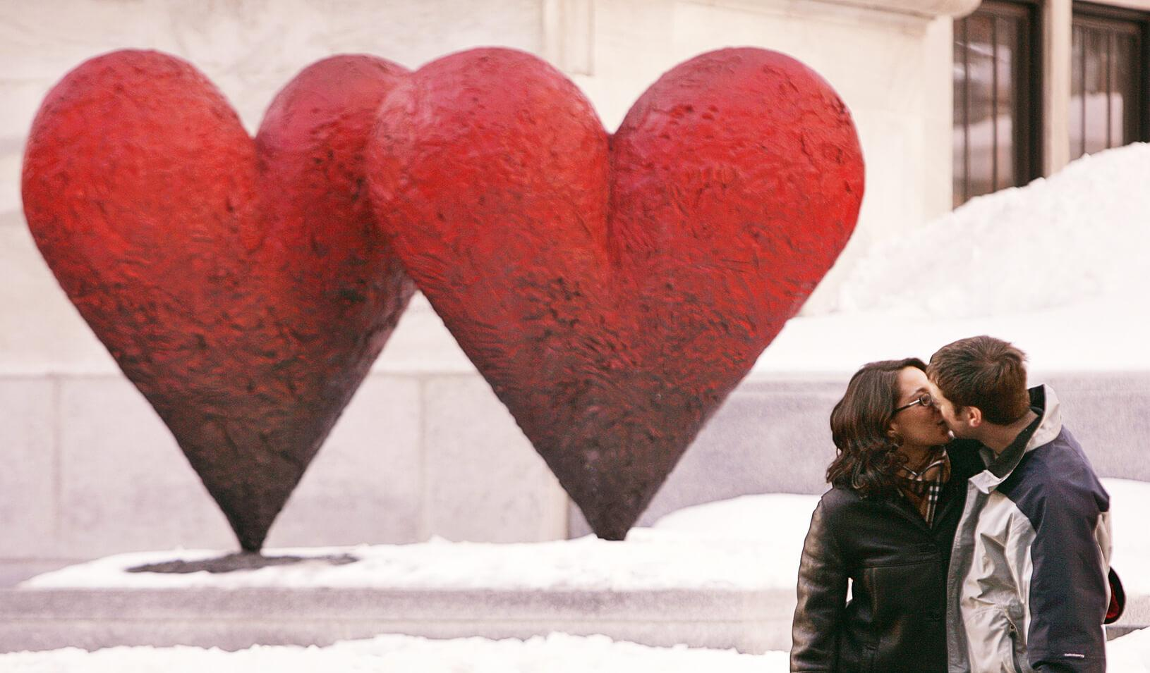 Couple kisses in front of a heart-shaped sculpture