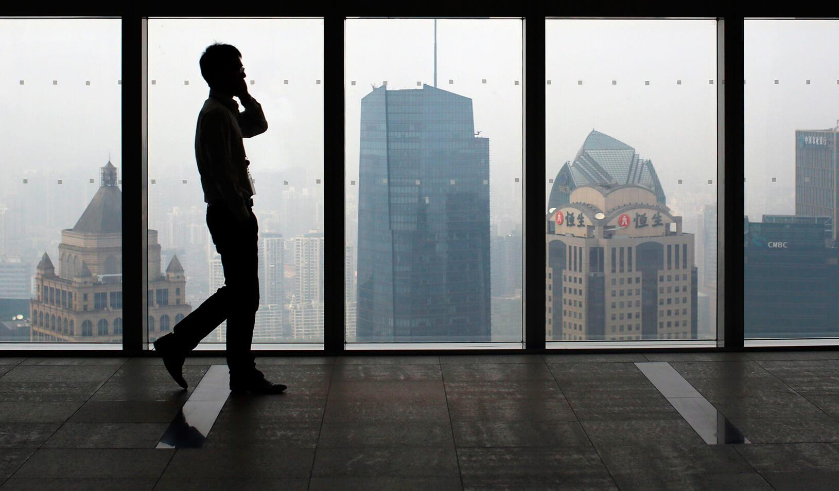 A man talks on a mobile phone as he walks past the view of the Shanghai skyline.