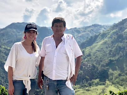 Maria Palacio and a coffee bean farmer stand side by side smiling, overlooking lush green mountains in Colombia. Courtesy of Maria Palacio