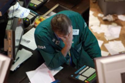 A NYSE trader with head in his hands