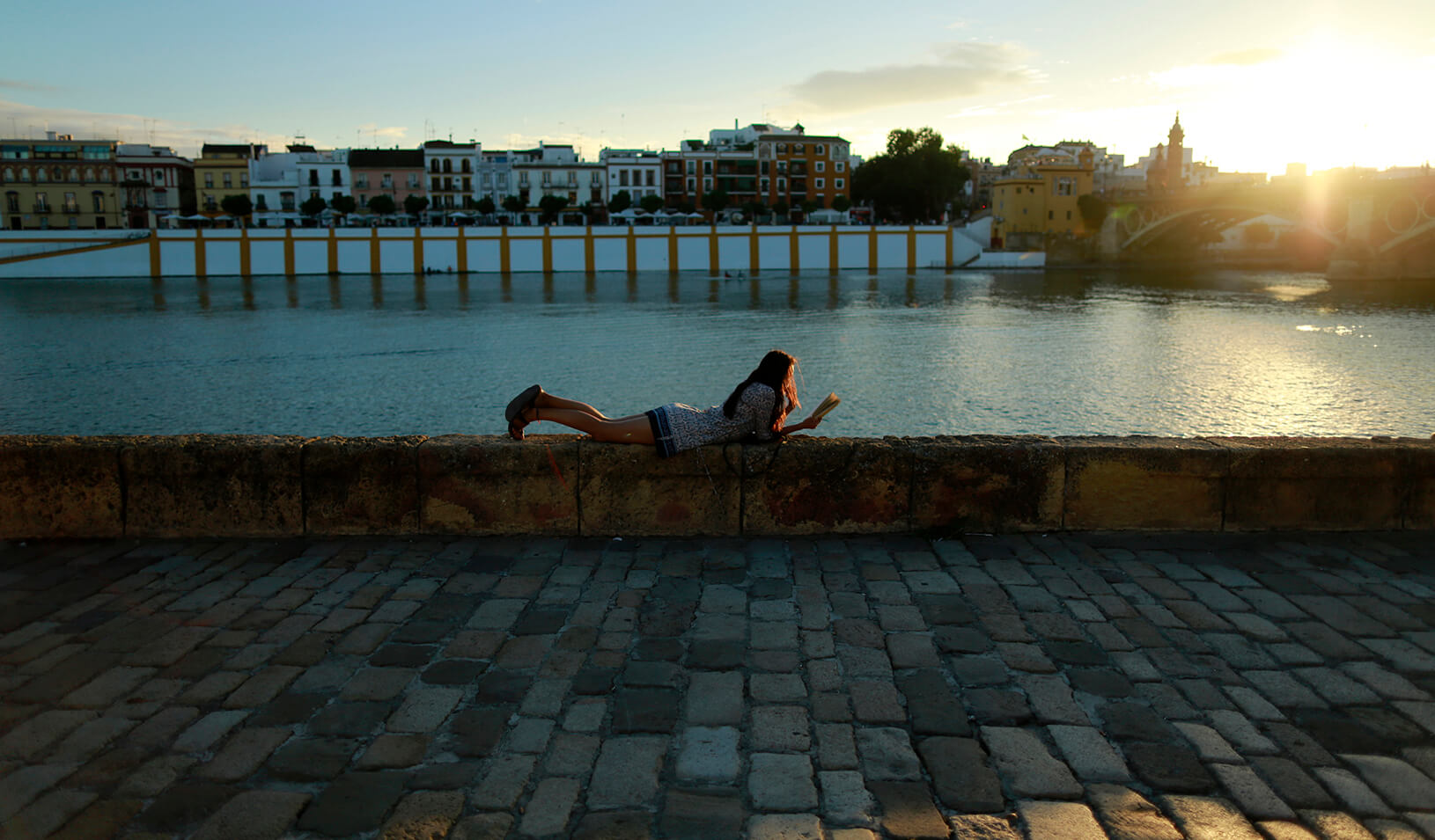 A woman leisurely reading a book. Reuters | Marcelo del Pozo