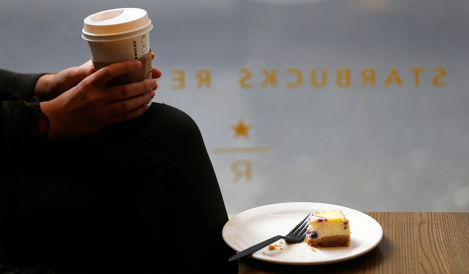 A customer cradles her drink at a Starbucks in central London. (Reuters photo by Andrew Winning)
