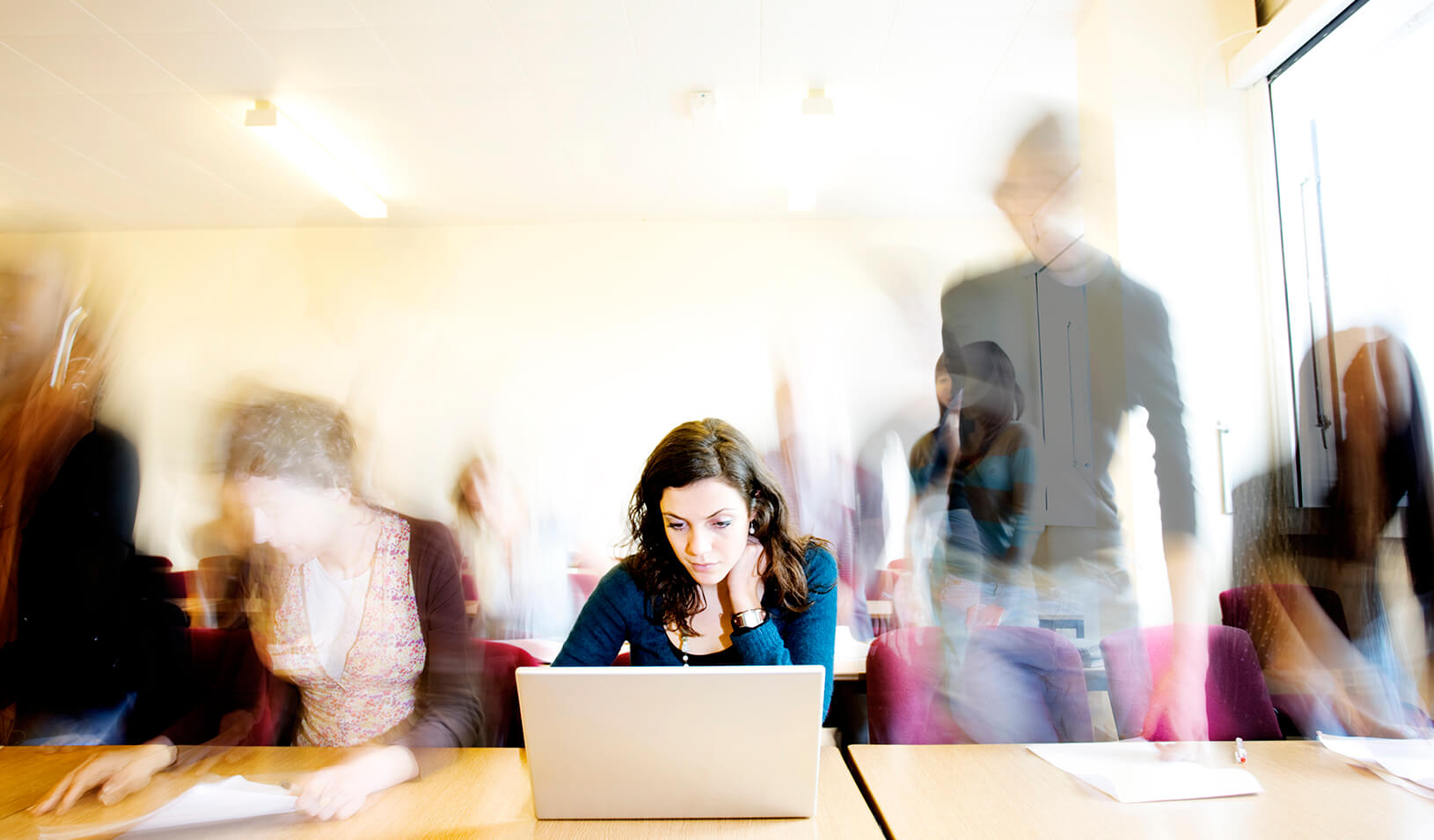 A student in front of her computer | iStock/Rene Mansi