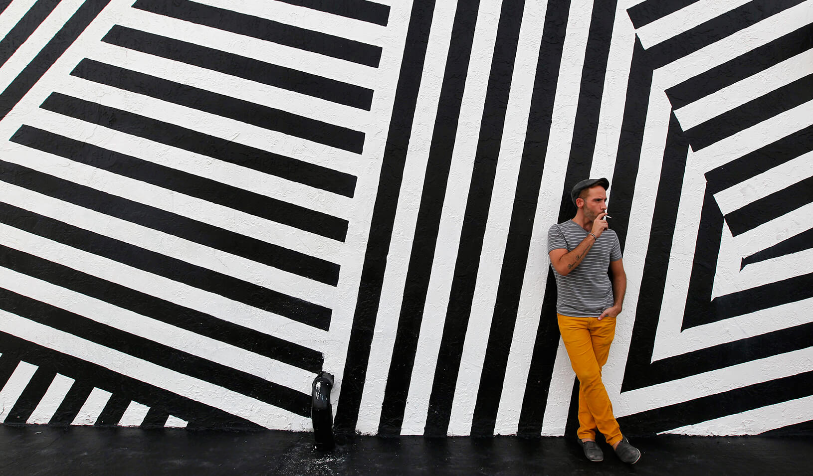 A man smokes a cigarette outside a building in Wynwood, a Miami neighborhood transformed by an influx of artists and visionary real estate developers | Reuters/Andrew Innerarity