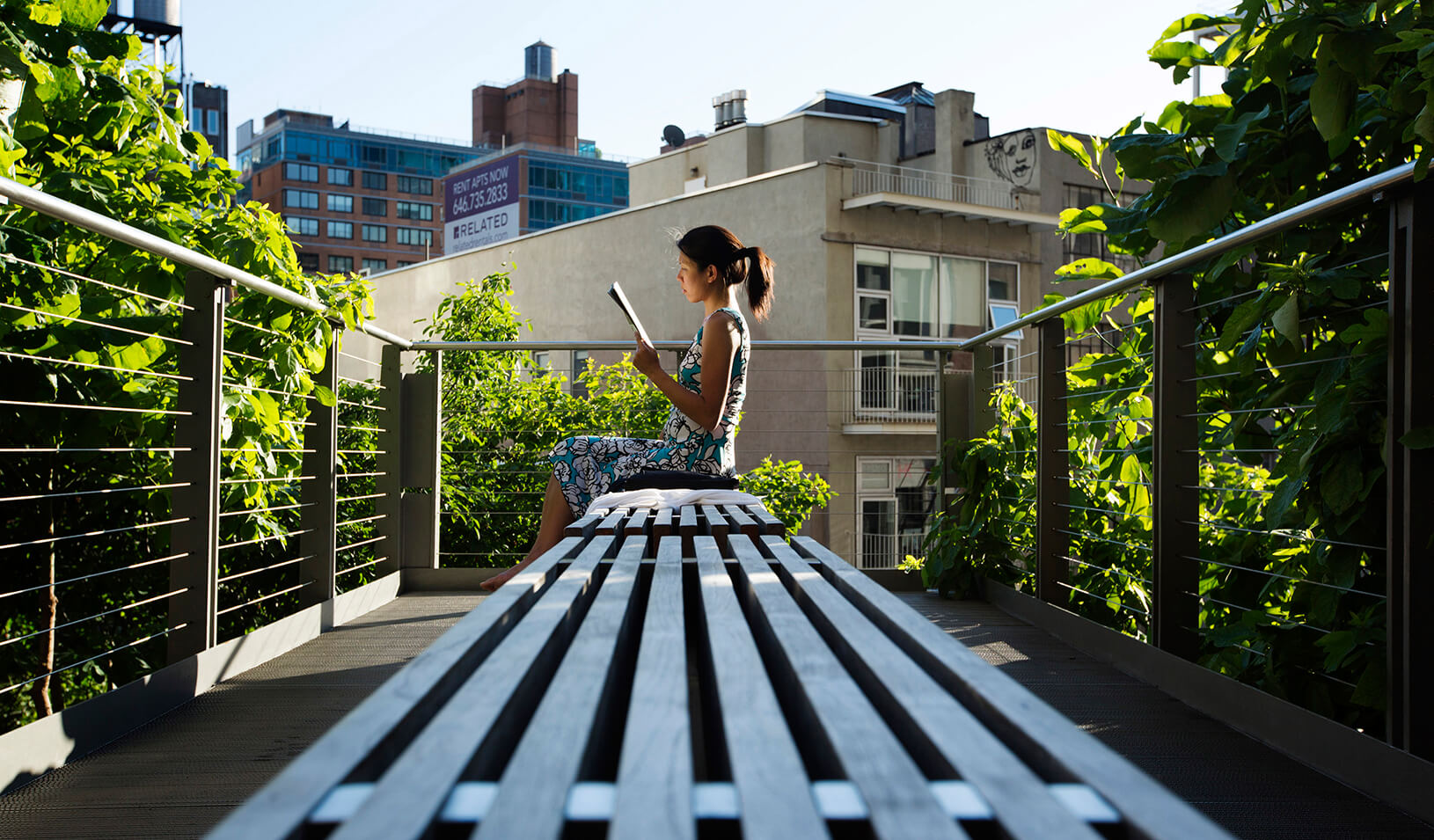 A woman uses the late afternoon sun to read while sitting on the High Line park in New York | Reuters/Lucas Jackson