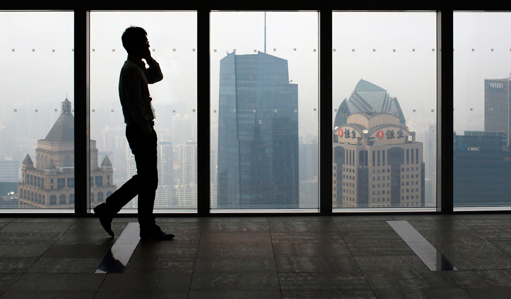 A man talks on a mobile phone as he walks past the view of the Shanghai skyline. | Reuters/Carlos Barria