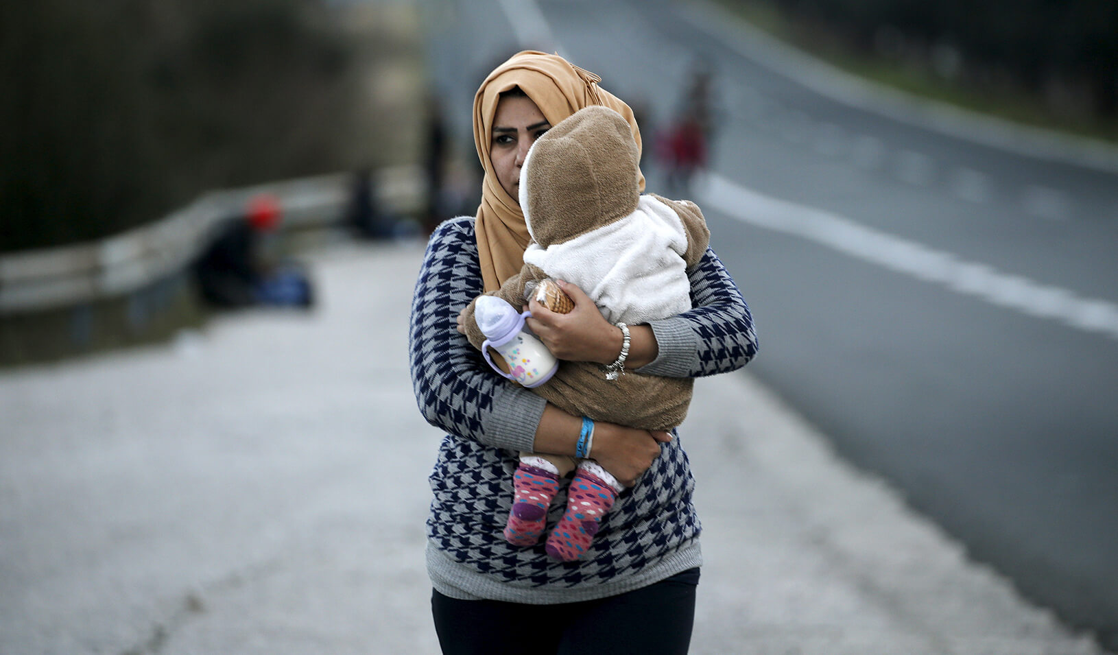 A refugee mother carrying her child | Reuters/Yannis Behrakis